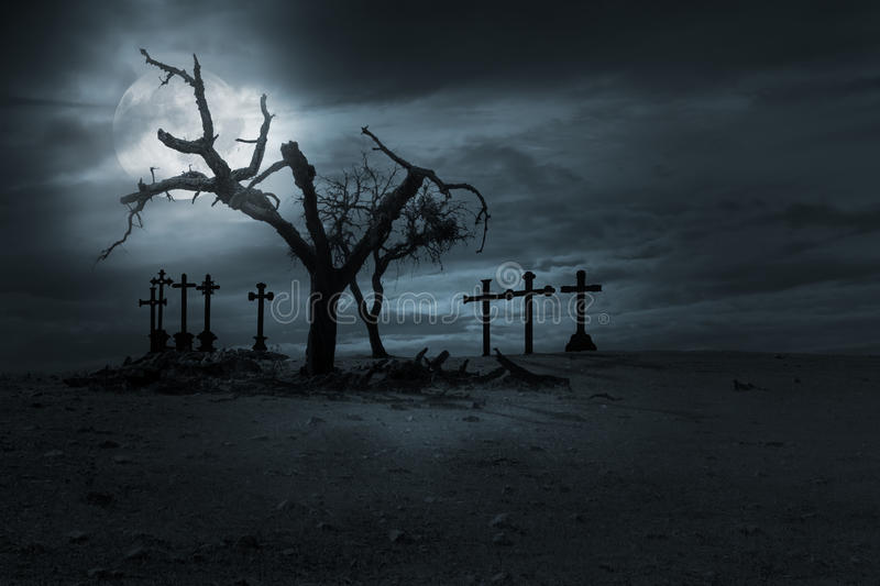 Halloween nght background. Spooky naked trees and christian cemetery crosses against a cloudy sky in a full moon night. Good as halloween background stock photo
