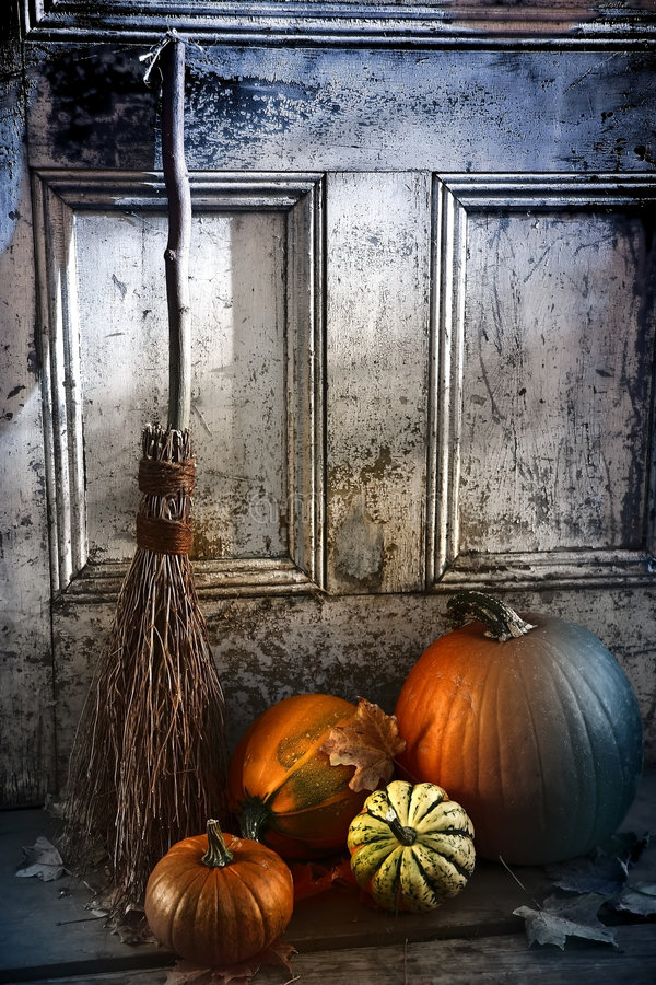 Halloween night. Pumpkins, broom and gourds at the door ready for halloween stock images