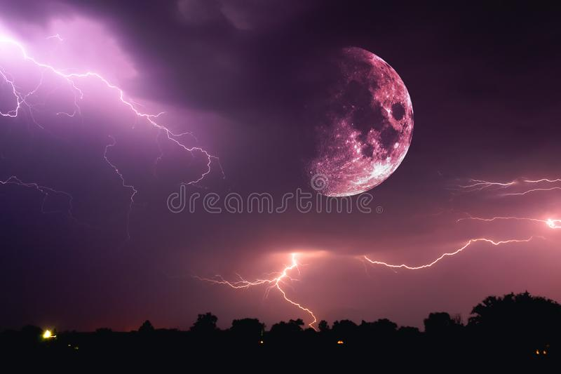 Halloween night sky with clouds and flashes of lightning and an emerging bloody red full moon closeup at the time of the Sabbath stock images