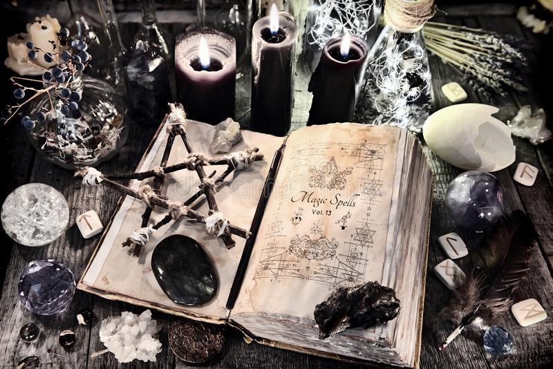 Open witch book with pentagram, black candles, stones, crystals and magic ritual objects stock photos