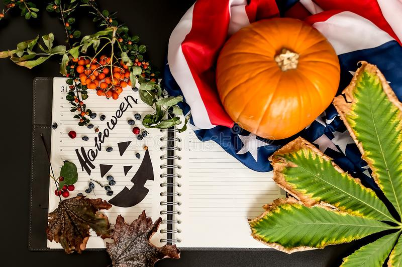 Halloween.an orange pumpkin with an American flag, a writing pad with a black Jack painted on it. the dry leaves empty space.  stock photos