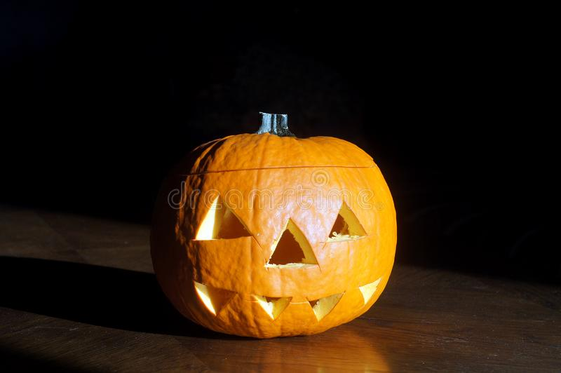 Halloween orange pumpkin head at dark background. Jack o Lantern photo with toothy scary face and shadow royalty free stock image