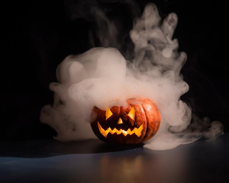 Halloween, orange pumpkin with a scary luminous face on a dark background. Thick gray smoke comes out and spreads across the black. Table. A close-up of a stock images