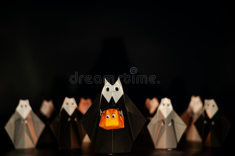 The Halloween origami or Paper folding Nun holding pumpkin head jack-o-lantern made from folded paper with many nuns at the stock images