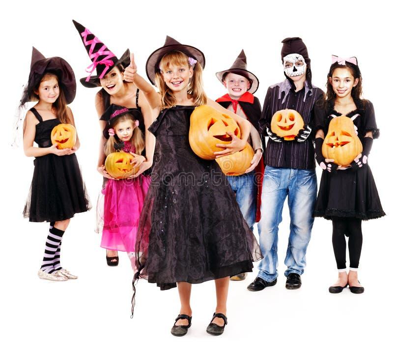 Halloween-Partei mit dem Gruppenkind, welches das Schnitzen des Kürbises hält. lizenzfreie stockbilder