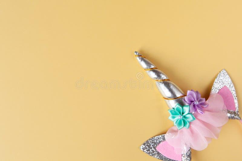 Halloween-Party-Accessoire, Felge mit Ohren und Einhornhorn. Pastellgelber Hintergrund, Kopierraum. Ferienwohnung. Minimaler Stil lizenzfreie stockbilder