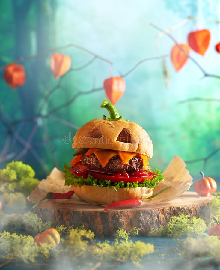 Halloween party burger in shape of scary pumpkin   on natural wooden board. Halloween food concept. Halloween party burger in shape of scary pumpkin   on natural royalty free stock photo