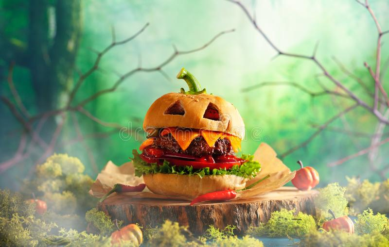 Halloween party burger in shape of scary pumpkin   on natural wooden board. Halloween food concept stock images