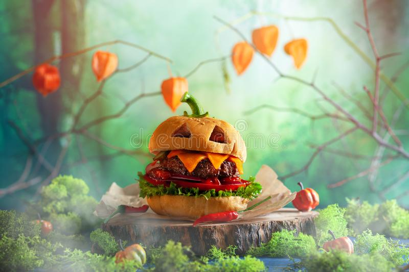 Halloween party burger in shape of scary pumpkin   on natural wooden board. Halloween food concept royalty free stock photo