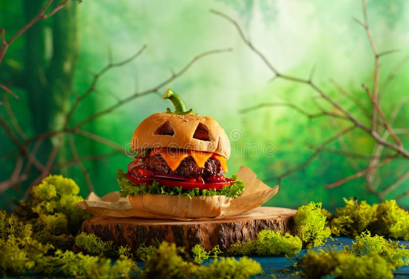 Halloween party burger in shape of scary pumpkin  on  wooden board. Halloween food concept royalty free stock images
