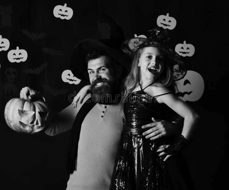 Halloween party and celebration concept. Father and daughter in costumes. Wizard and little witch stock image