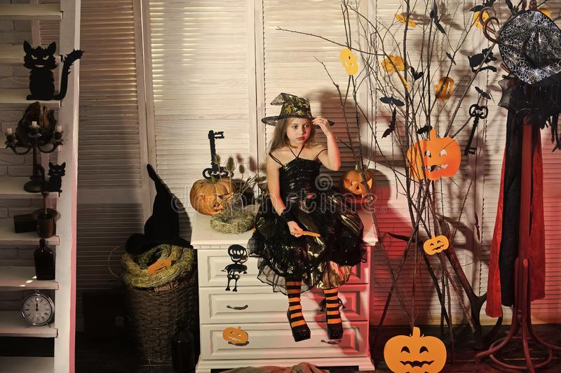 Halloween party and celebration concept. Girl with confused face. On spooky carnival room background. Kid in witch hat and costume sits on chest of drawers royalty free stock photos