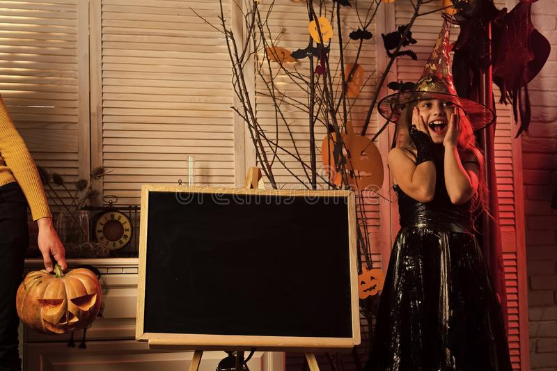 Halloween party and celebration concept. Kid in witch hat. And costume near chalkboard. Girl with troubled face on spooky carnival room background, copy space stock photo