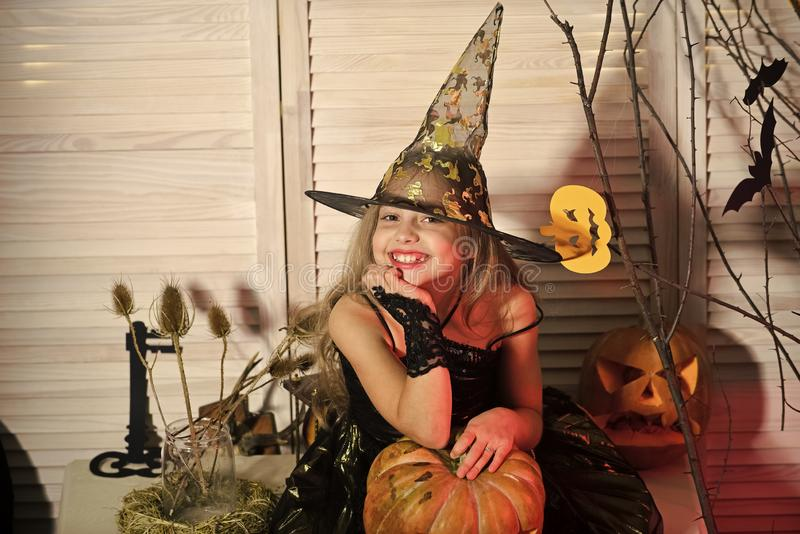 Halloween party and celebration concept. Little witch with Halloween decor. Girl with smiling face on spooky carnival room background. Kid in witch hat and stock image