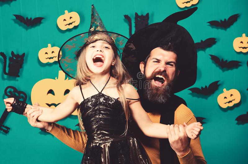 Halloween party and celebration concept. Wizard and little witch. In black hats dance. Girl and bearded men with cheerful faces on green background with decor stock photo