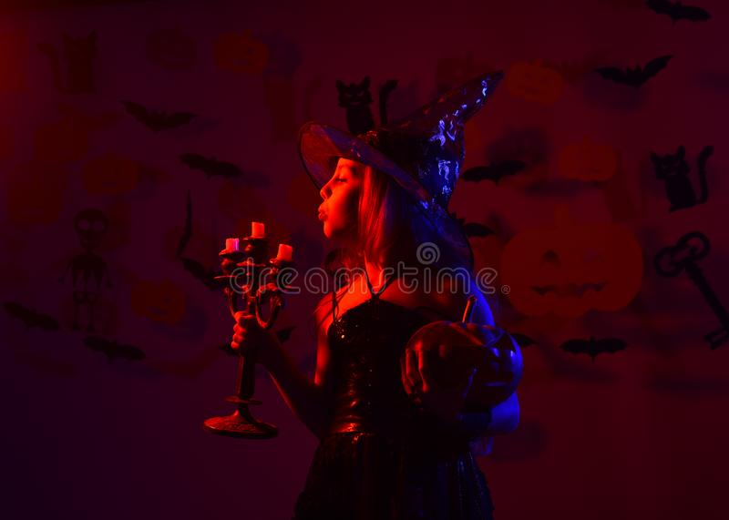 Halloween party concept. Girl with busy face on bloody red. Background with decor. Kid in spooky witches costume blows on candles holding jack o lantern and stock photography