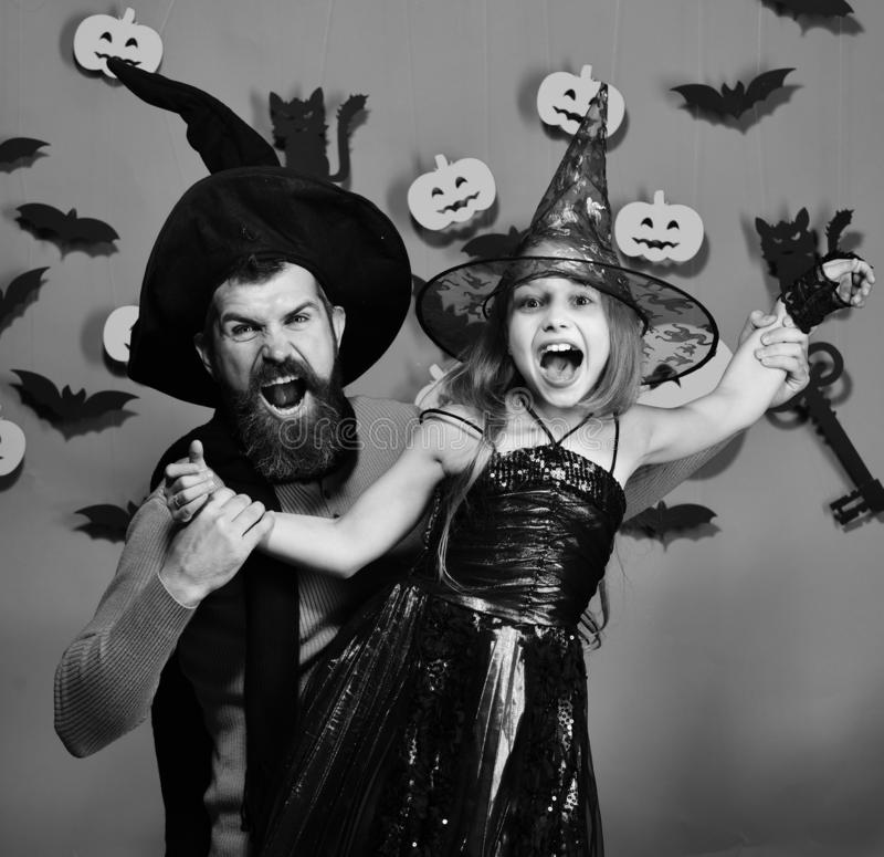 Halloween party concept. Wizard and little witch in black hats royalty free stock photography