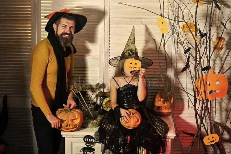 Halloween party concept. Wizard and little witch in hats. Hold jack o lanterns. Girl and men with happy and hidden faces on red spooky carnival room background royalty free stock photography