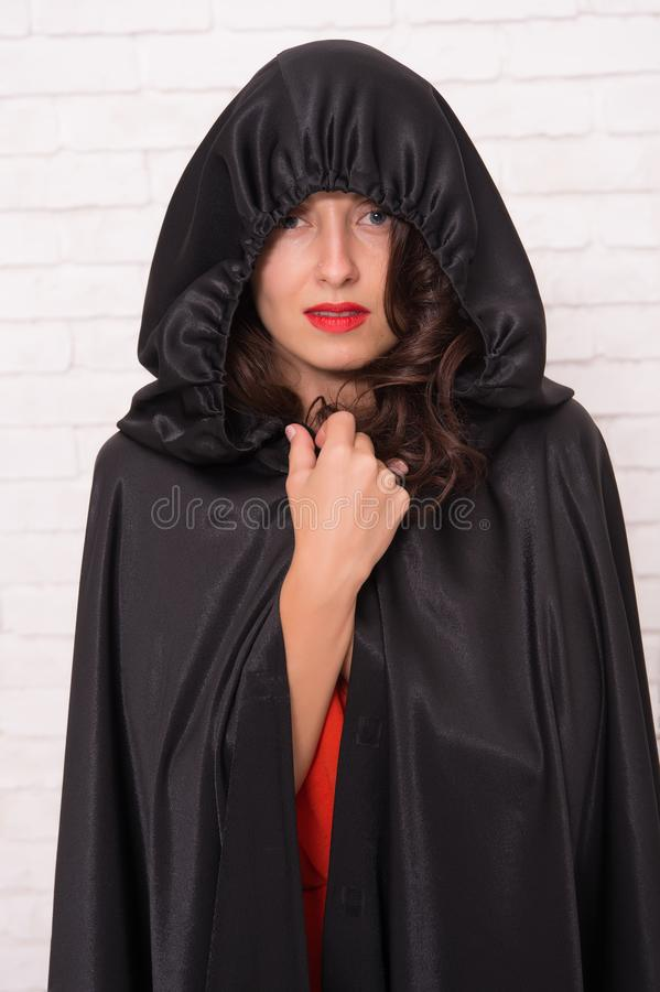 Halloween party. Damn pretty woman devil. Death in black cloak symbol. Vampire in cloak sexy devil girl. Woman tempting stock images