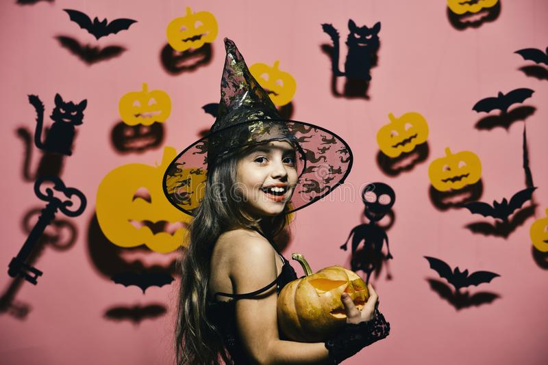 Halloween party and decorations concept. Girl with happy face on pink background with bats, pumpkins stock photos