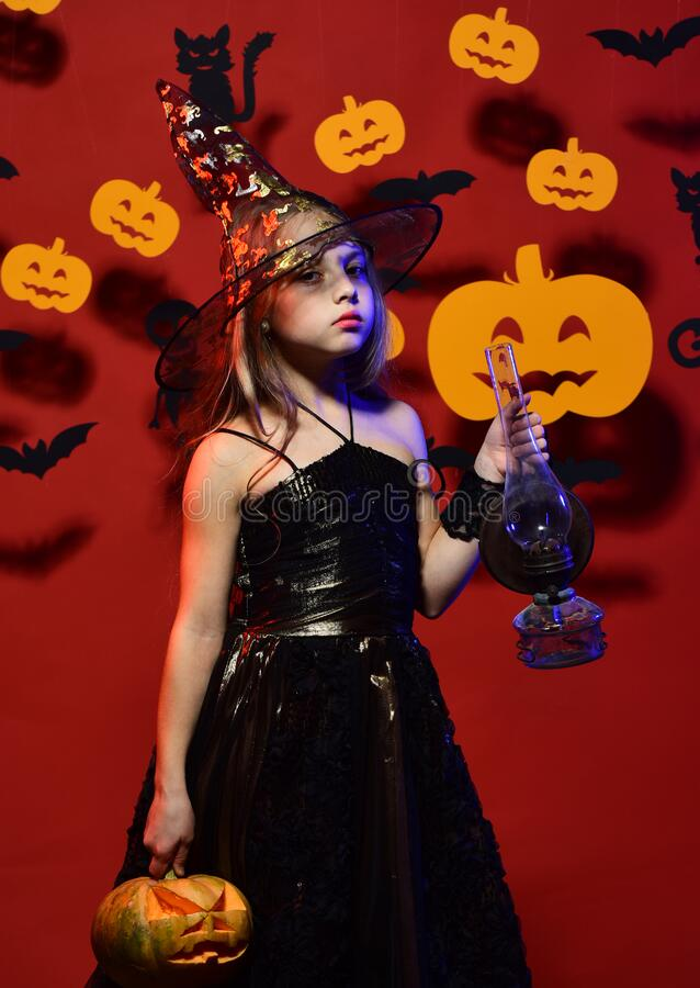 Halloween party and decorations concept. Kid in spooky witches costume royalty free stock photo