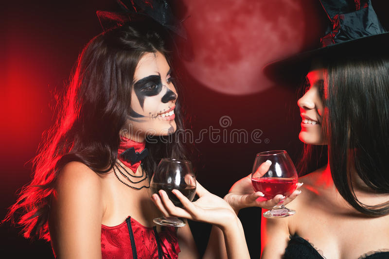 Halloween party 2016! Fashion women like witch holding cocktail. Of blood. Makeup. Halloween costumes. Role. Witch carnival costume. Role-playing games. babes royalty free stock photo