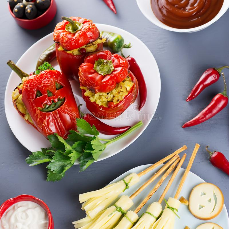 Halloween party food. Red stuffed peppers with scary cutout faces, witches brooms of cheese and other treats stock images