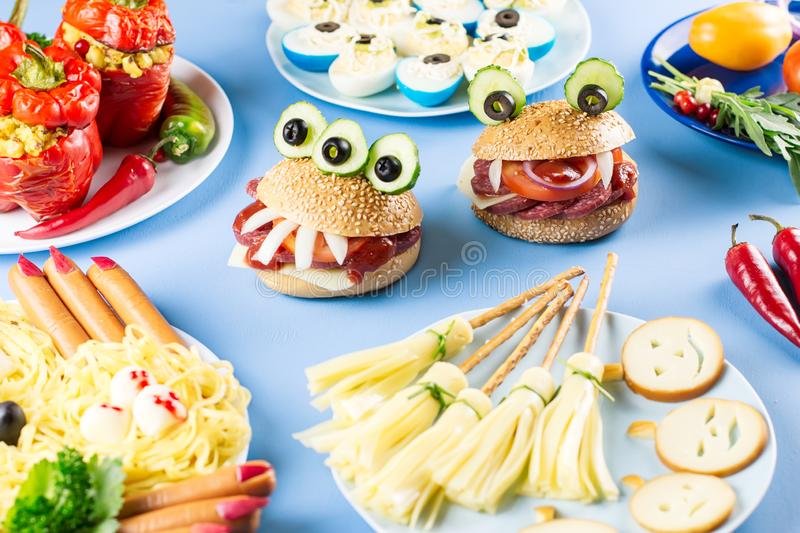 Halloween party food. Stuffed peppers with scary faces, cheese witches brooms, monster hamburgers, witch finger treats. royalty free stock images