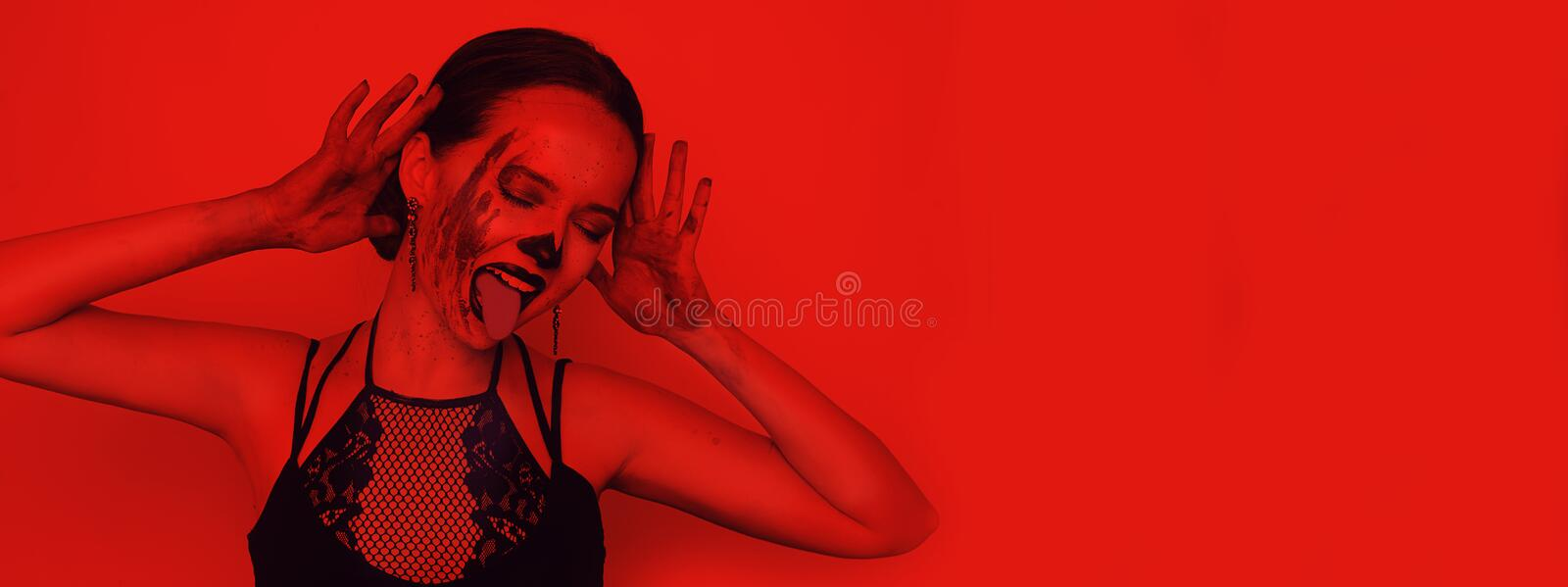 Halloween party, girl in costume and with halloween make-up. Girl in red neon in the blood and with a skeleton make-up. Girl shows royalty free stock photography