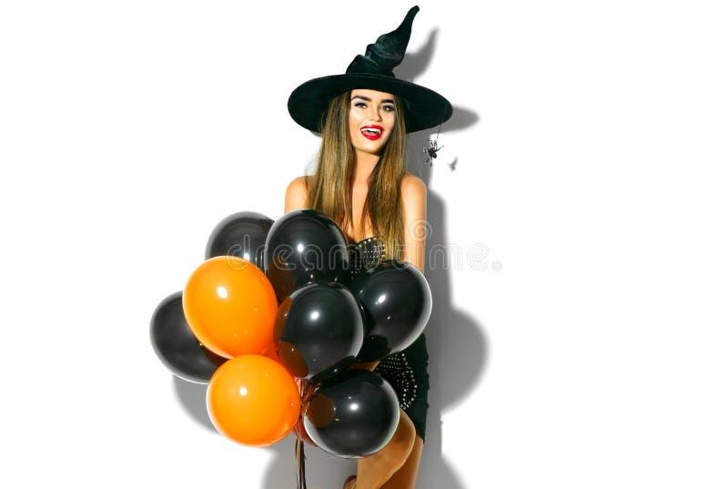 Halloween-Party-Girl Sexy Hexe, welche die schwarzen und orange Luftballone hält lizenzfreie stockfotografie