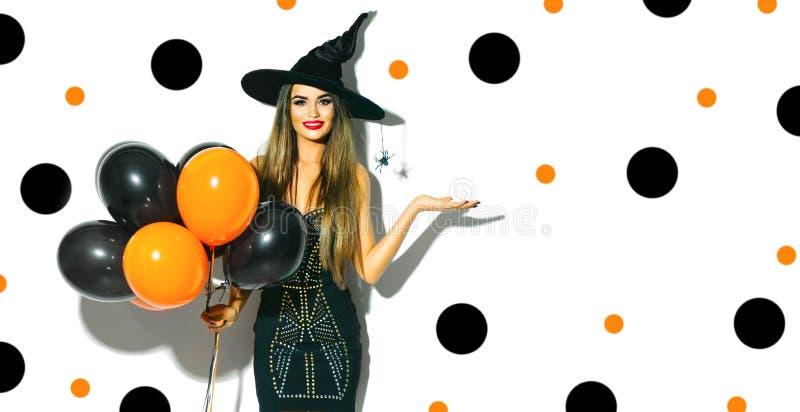 Halloween-Party-Girl Sexy Hexe, welche die schwarzen und orange Luftballone hält stockfotografie