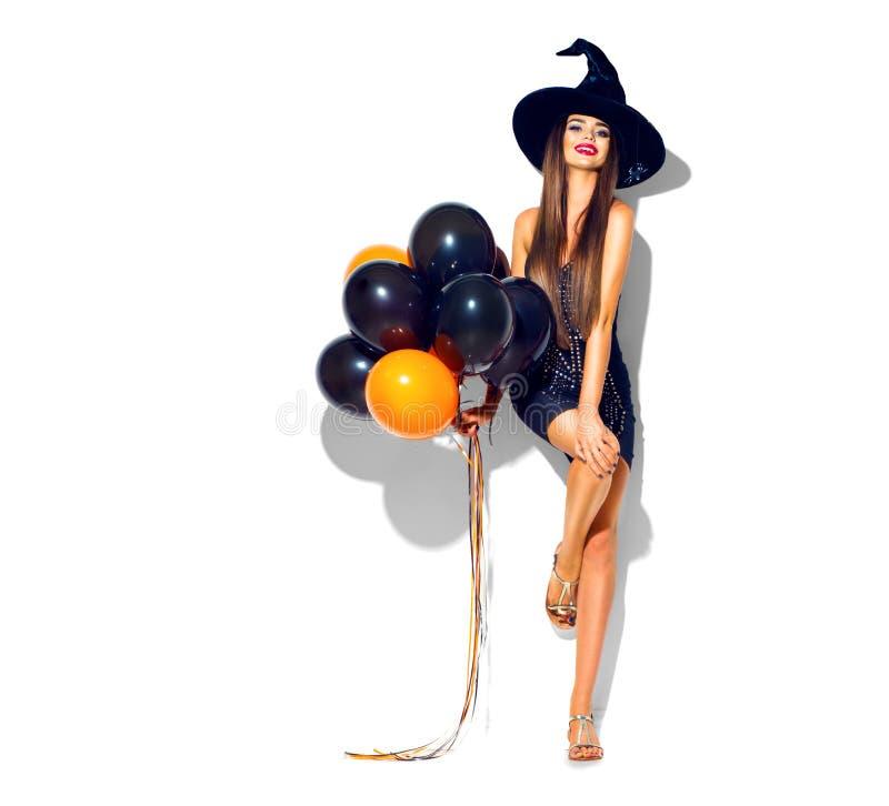 Halloween-Party-Girl Sexy Hexe, welche die schwarzen und orange Luftballone hält stockfoto