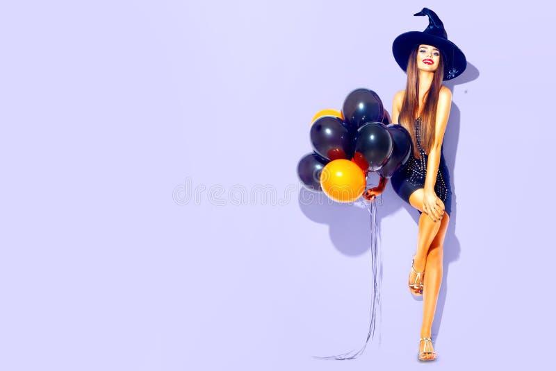 Halloween-Party-Girl Sexy Hexe, welche die schwarzen und orange Luftballone hält stockbilder