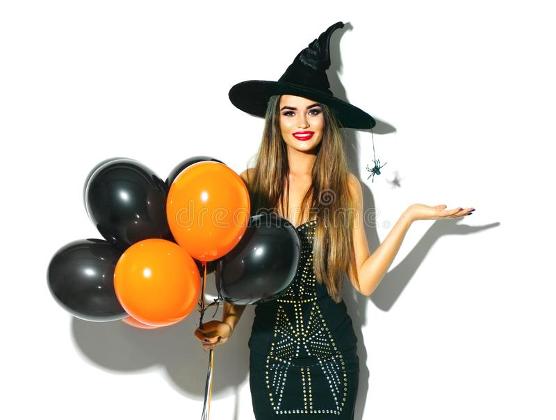 Halloween party girl. witch holding black and orange air balloons royalty free stock photo