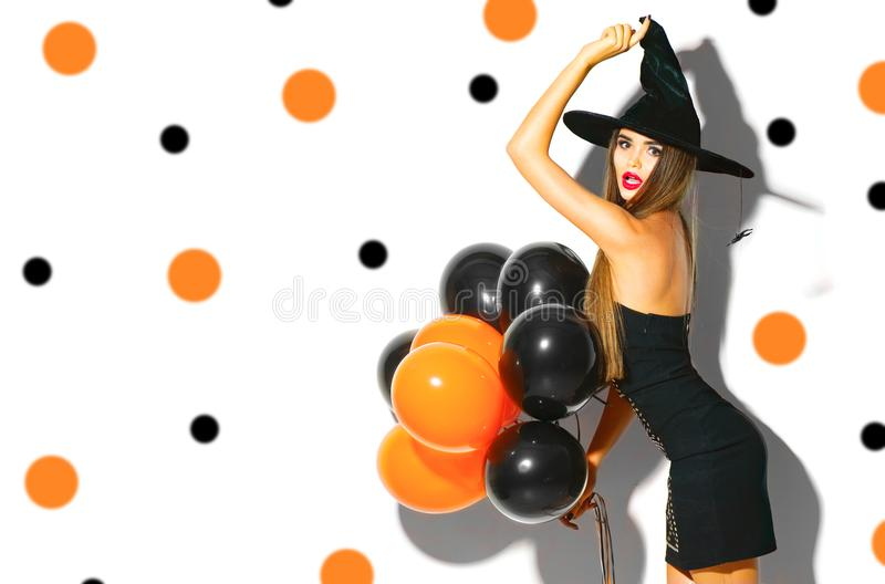 Halloween party girl. witch holding black and orange air balloons royalty free stock image