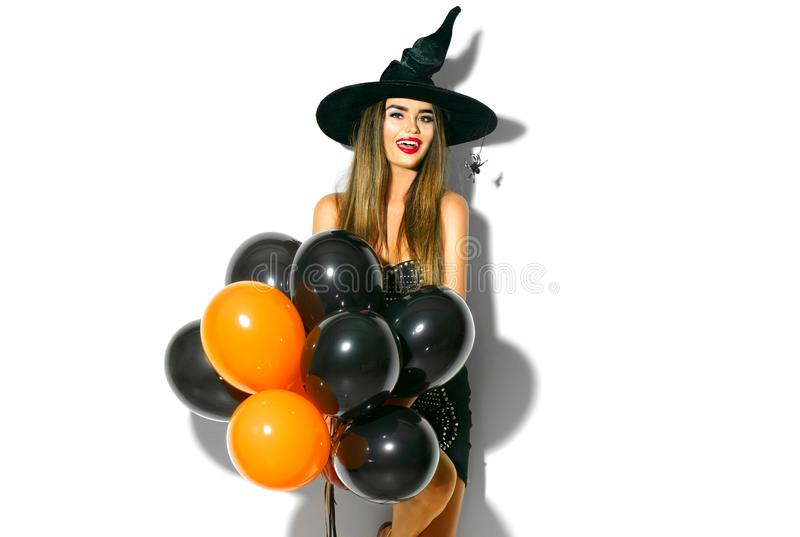 Halloween party girl. witch holding black and orange air balloons. Beautiful young woman in witches hat and costume royalty free stock photography
