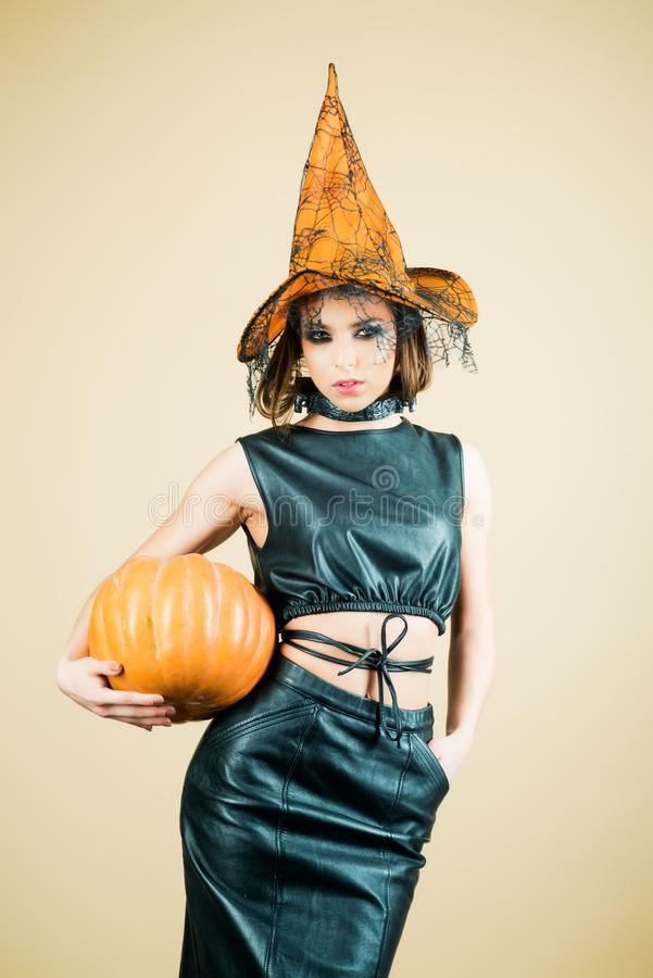 Halloween Party girl. Witch hat. Happy Halloween witch with pumpkin. Young woman with witch hat dressed as vampire for stock image