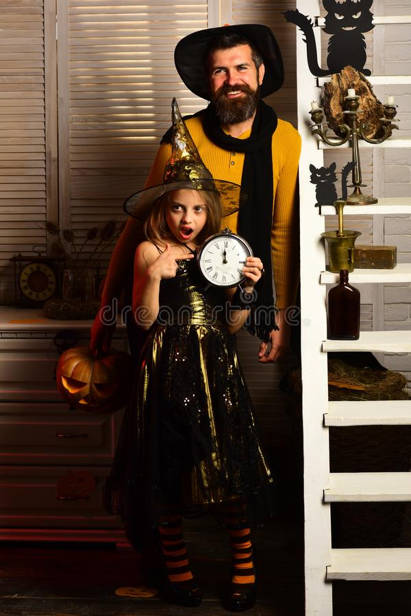 Halloween party: little witch and bearded magician royalty free stock photos