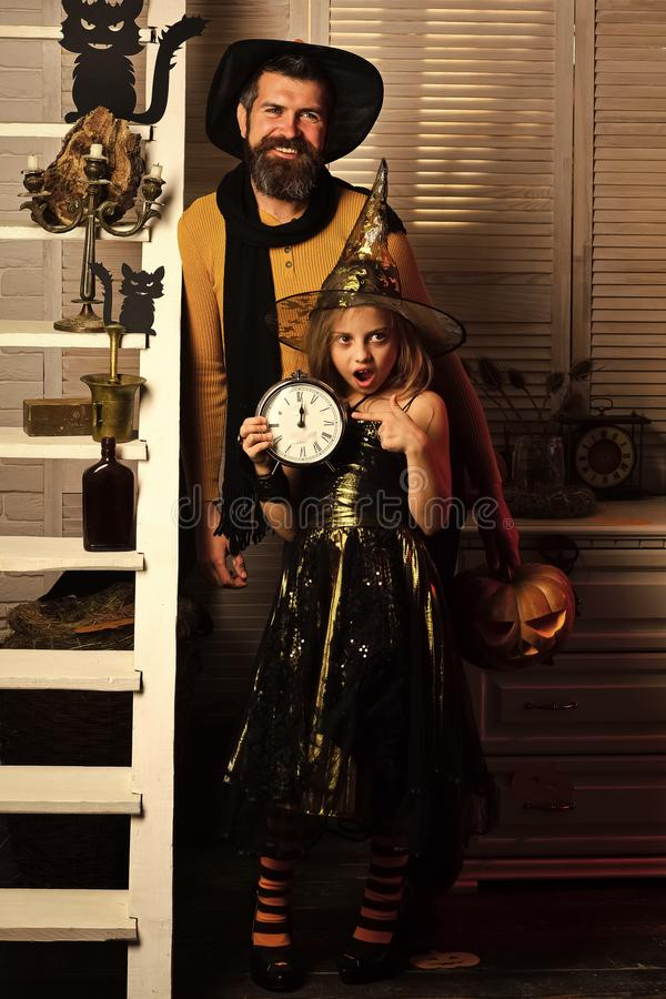 Halloween party: little witch and bearded magician stock photo