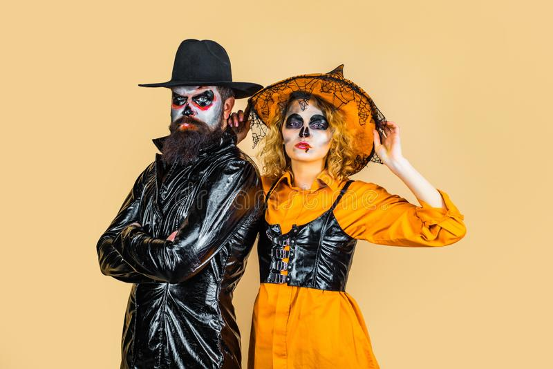 Halloween Party people. Halloween surprised woman and handsome bearded man in Halloween hat and costume holding pumpkin. stock photos