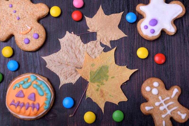Halloween-peperkoekkoekjes met multicoloured verglazing en droge esdoornbladeren dat worden verfraaid royalty-vrije stock foto's