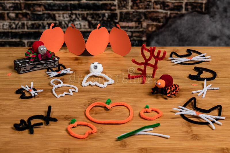 Halloween pipe-cleaner and construction paper crafts featuring Black Cats, pumpkins, ghosts, spiders and the devil. Handmade crafts for the fun of family time stock photo