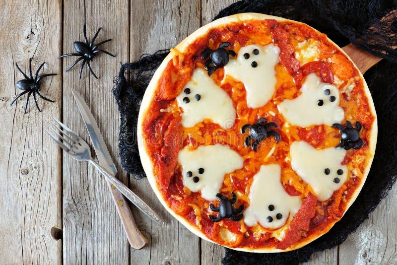 Halloween-Pizza über Szene mit Dekor auf rustikalem Holz lizenzfreies stockfoto