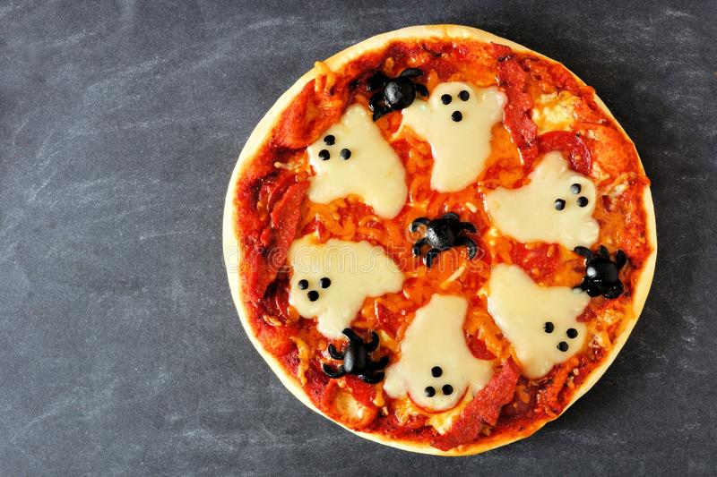 Halloween pizza overhead view on slate royalty free stock image