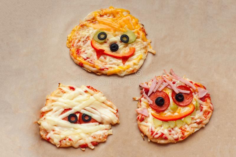 Halloween-pizza met monsters, boven scène met decor op een ambachtdocument vakje achtergrond, idee voor het gezonde voedsel van d stock afbeelding