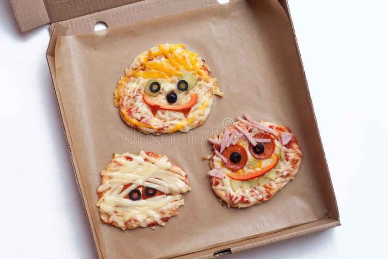 Halloween-Pizza mit Monstern, über Szene mit Dekor auf einem Kraftpapierkastenhintergrund, Idee für das Hauptparteilebensmittel,  lizenzfreie stockfotos