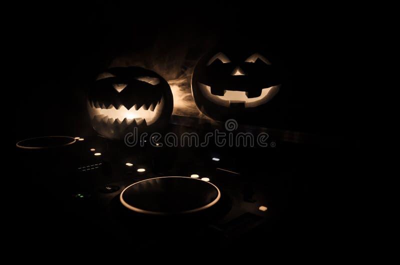 Halloween-pompoen op een lijst van DJ met hoofdtelefoons op donkere achtergrond met exemplaarruimte Gelukkige Halloween-festivald stock foto
