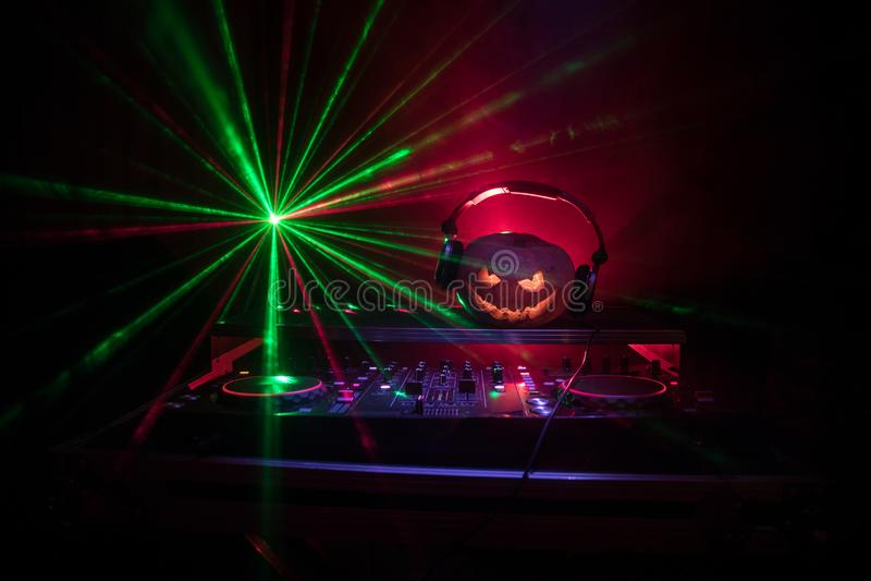 Halloween-pompoen op een lijst van DJ met hoofdtelefoons op donkere achtergrond met exemplaarruimte Gelukkige Halloween-festivald royalty-vrije stock afbeelding