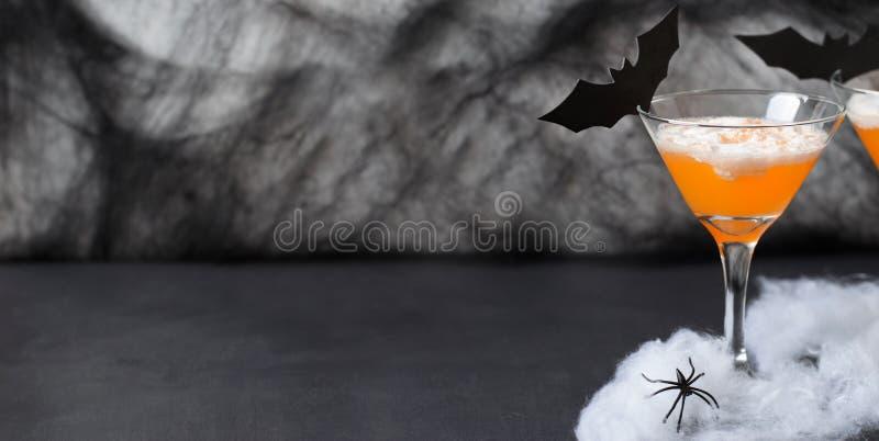 Halloween-Pompoencocktail, Giftige Oranje die Drank met Spinnen wordt verfraaid, Spinneweb en Zwarte Knuppels op Donkere Achtergr stock foto's