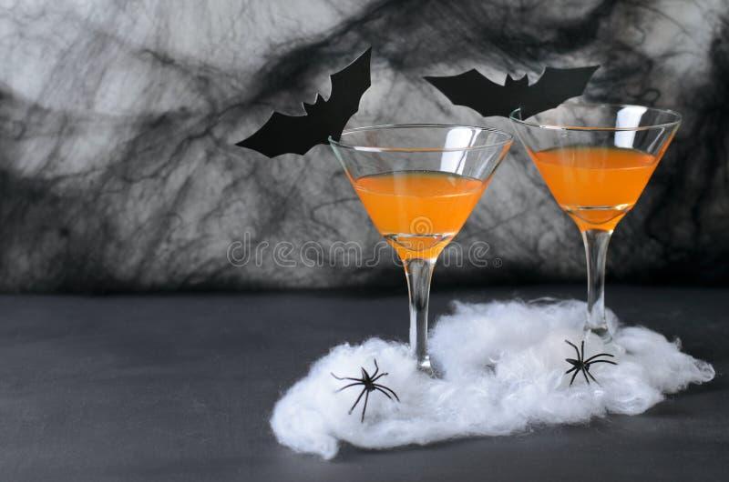 Halloween-Pompoencocktail, Giftige Oranje die Drank met Spinnen wordt verfraaid, Spinneweb en Zwarte Knuppels op Donkere Achtergr royalty-vrije stock afbeelding